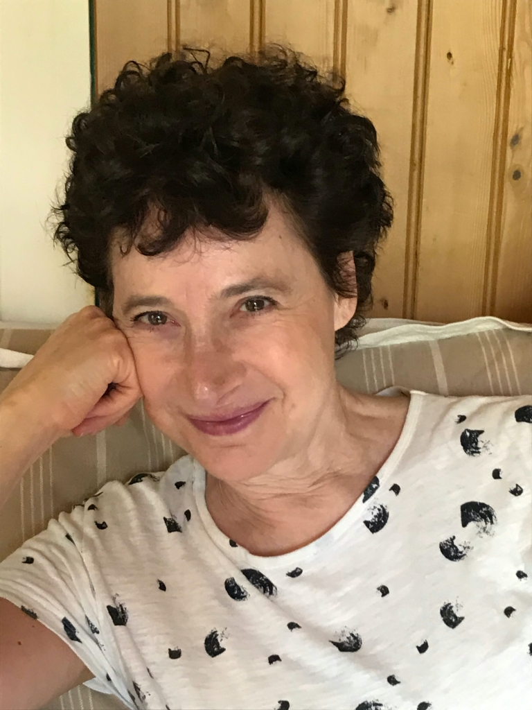 Anna Ciddor sits in a chair, wearing a white shirt with black spots, and is smiling at the camera. She is a white woman with dark, curly hair.