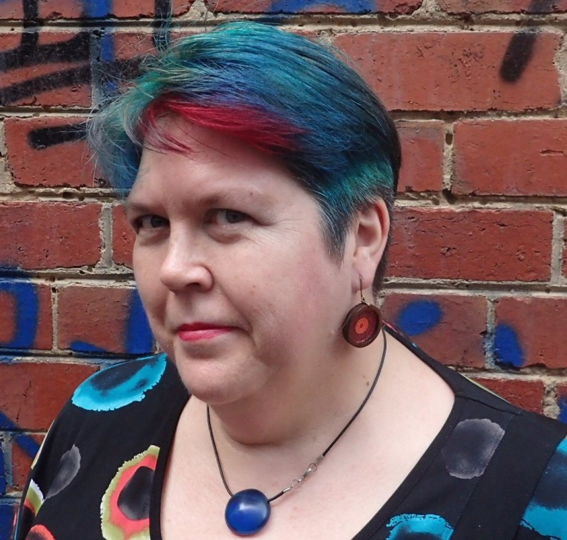 A woman stands in front of a brick wall. She has short red, blue and green hair, and wears a black shirt with red and blue spots.