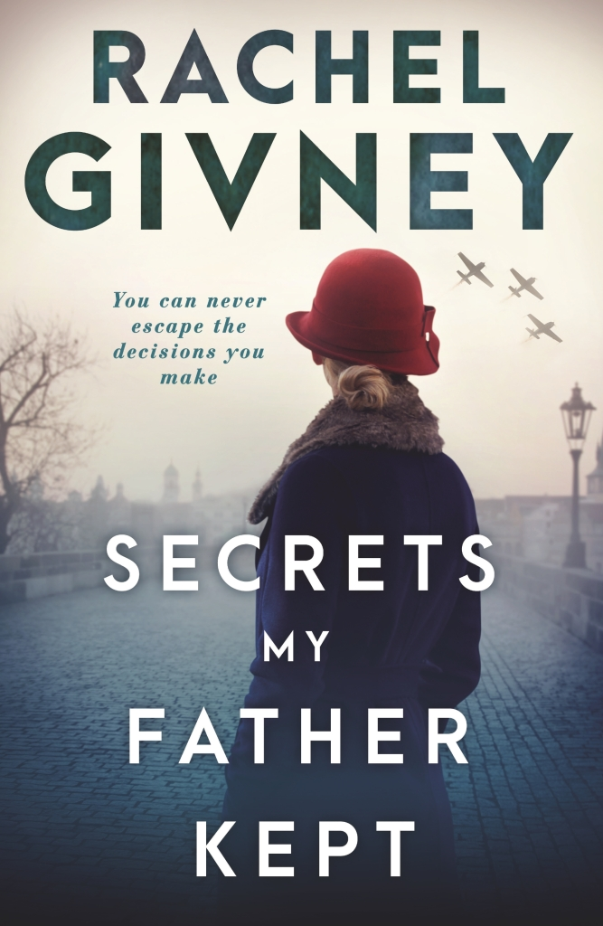 A young girl in a blue coat and red hat stands on a cobblestone street looking back at a city shrouded in mist. The title Secrets My Father Kept is in white in front of her. The author's name Rachel Givney is in green above her. The tag line reads You can never escape the decisions you make.