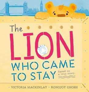 A lion peaks over the top of a yellow box with the London skyline in blue behind it. On the yellow crate it reads The Lion Who Came to Stay: Based on a True Story by Victoria McKinlay. Illustrated by Ronojoy Ghosh.