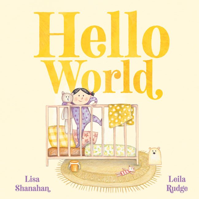 A yellow  cover with a brown cot with different coloured pillows. A little girl in purple clothes holding a toy cat stands in it under the yellow words Hello World. It is by Lisa Shanahan and Leila Rudge.