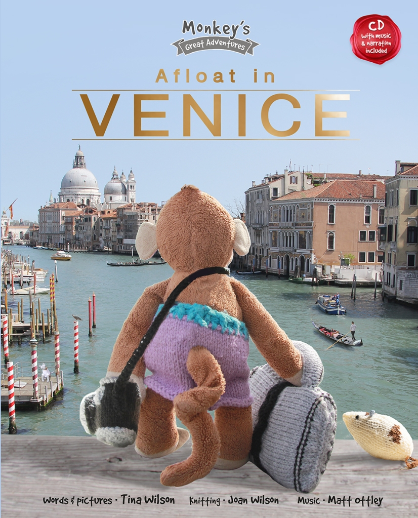 An image  of a canal surrounded by buildings with gondolas. A toy monkey in knitted purple oants with a knitted bag and knitted camera, next to a knitted mouse looks out over Venice. The title is Afloat in Venice by Tina Wilson. It is accompanied by a CD with music by Matt Ottley.