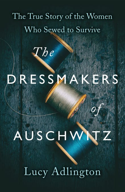 A dark blue cover with two spools of thread. One is grey and the other is blue. The White text reads The Dressmakers of Auschwitz by Lucy Adlington.